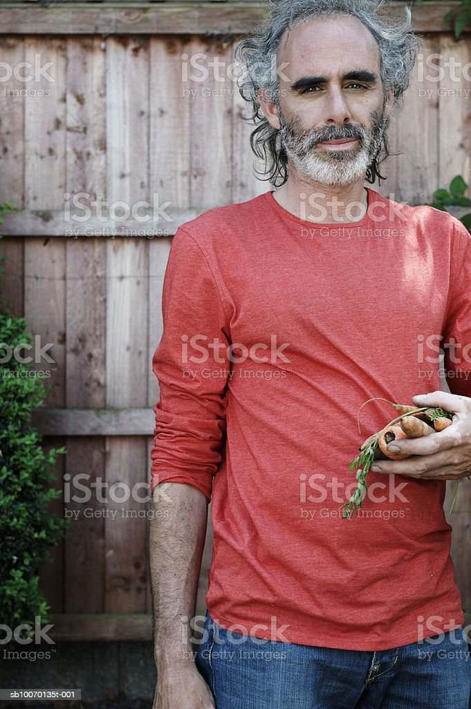 Portrait of mature man with carrots in front of fence royalty-free stock photo