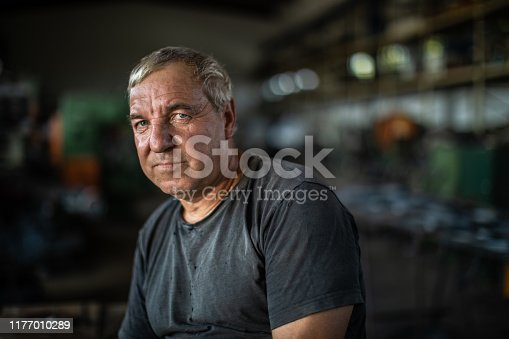 Portrait of mature manual worker in metal industry, sitting on table and looking at camera