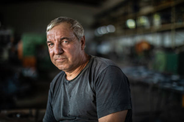 Portrait of mature manual worker in metal industry Portrait of mature manual worker in metal industry, sitting on table and looking at camera eastern europe stock pictures, royalty-free photos & images