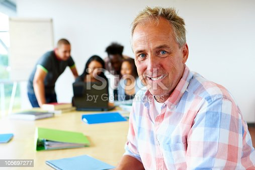 877026356 istock photo portrait of mature teacher with students behind 105697277