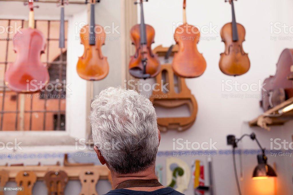 portrait of mature violin maker stock photo