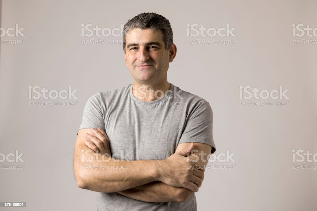 portrait of mature white man 40 to 50 years old smiling happy showing nice and positive face expression with folded crossed arms isolated on grey background in feelings and emotions concept stock photo