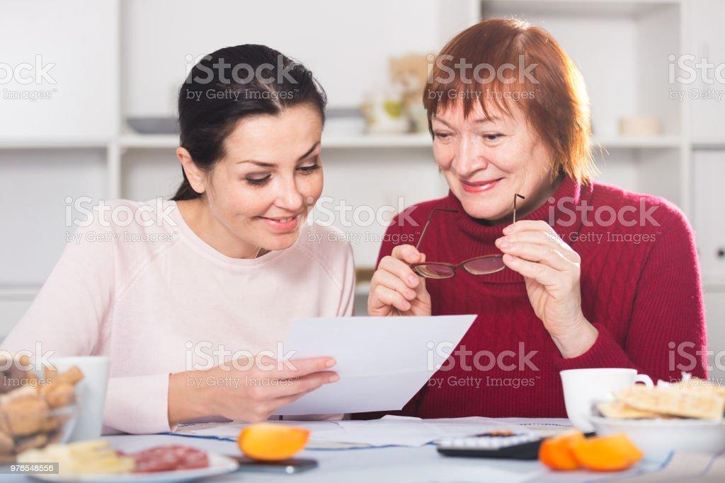 Retrato da mulher madura e filha com documentos - foto de acervo