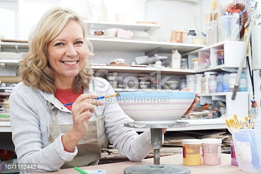 istock Portrait Of Mature Woman Decorating Bowl In Pottery Class 1071112442