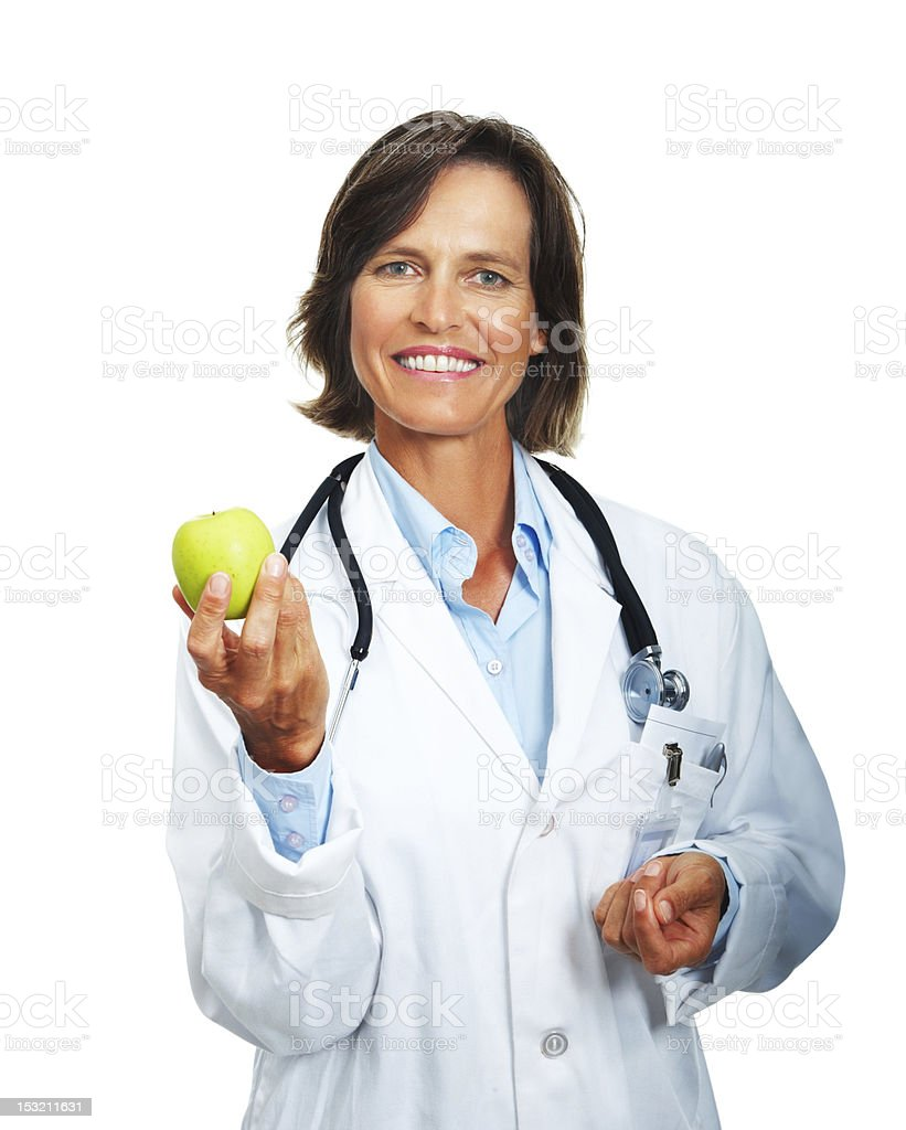 Portrait of mature woman doctor holding apple and smiling royalty-free stock photo