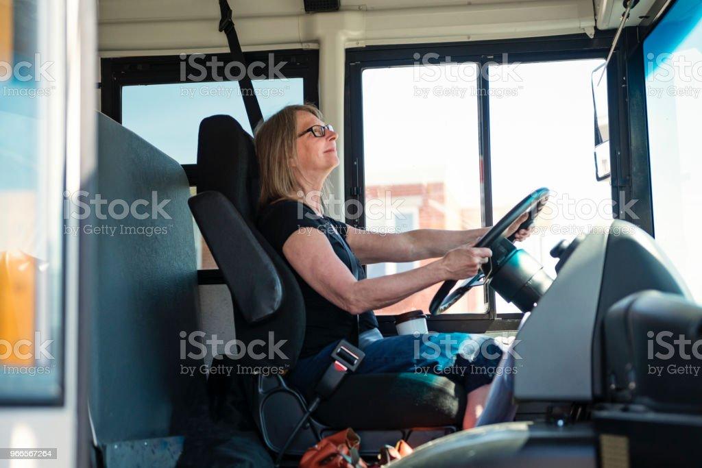 Retrato de mulher madura, dirigindo um ônibus escolar. - foto de acervo