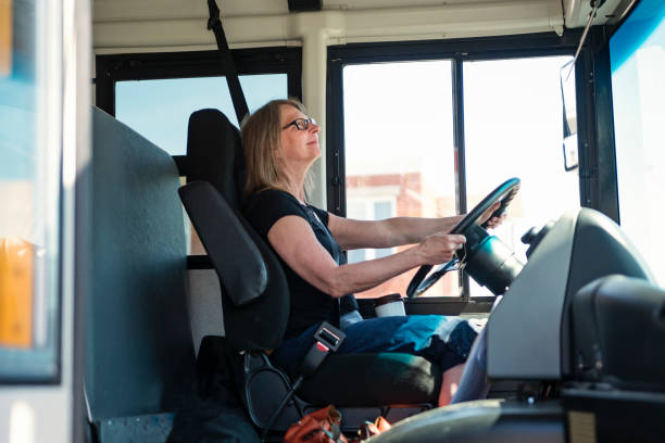 Portrait of mature woman driving a school bus. stock photo
