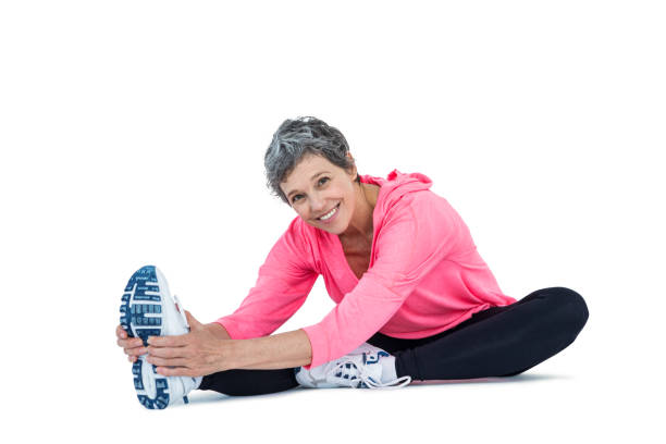 Portrait of mature woman exercising Portrait of mature woman exercising over white background touching toes stock pictures, royalty-free photos & images