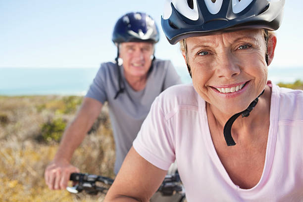 Portrait of mature woman in sports helmet smiling with man in background stock photo