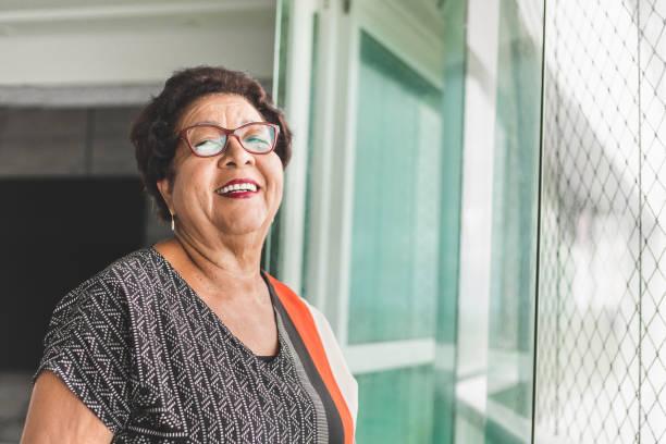 verticale de femme mûre regardant par la fenêtre - une seule femme senior photos et images de collection