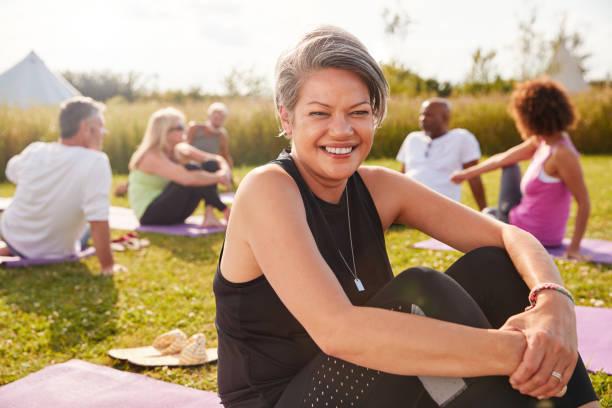 成熟女人的肖像戶外瑜伽撤退與朋友和露營地的背景 - 50多歲 個照片及圖片檔