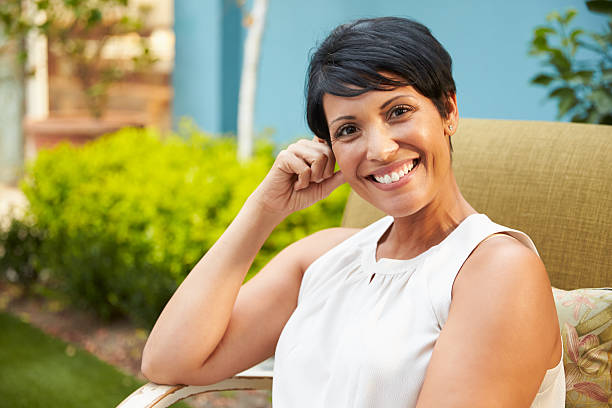 Portrait Of Mature Woman Relaxing Outdoors In Garden Portrait Of Mature Woman Relaxing Outdoors In Garden one mature woman only stock pictures, royalty-free photos & images