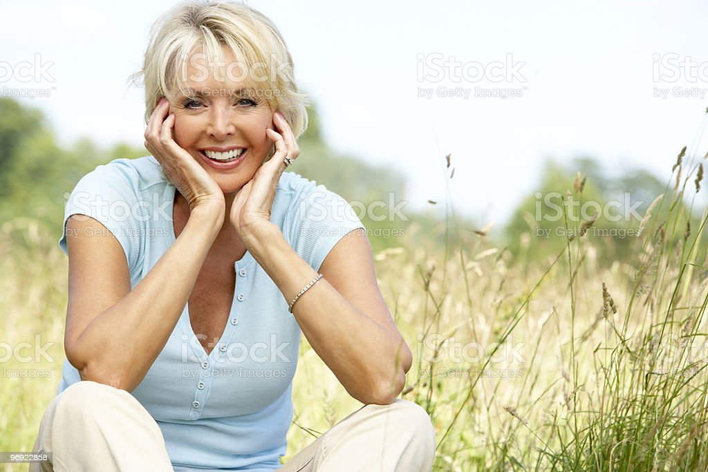 Portrait of mature woman sitting in countryside stock photo