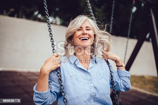 Smiling senior woman with gray hair sitting on swing, having fun and enjoying retirement