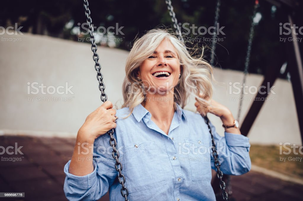 Portrait of mature woman with gray hair sitting on swing - foto stock