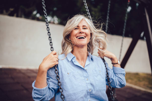 Portrait of mature woman with gray hair sitting on swing stock photo