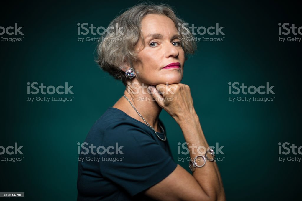 Portrait Of Mature Woman With Hand On Chin stock photo