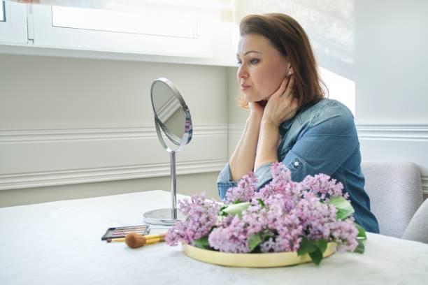 Retrato de mujer madura con maquillaje espejo masajeando su cara y cuello, hermosa hembra de 40 años de edad - foto de stock