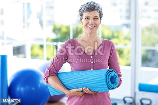 istock Portrait of mature woman with yoga mat 665619774