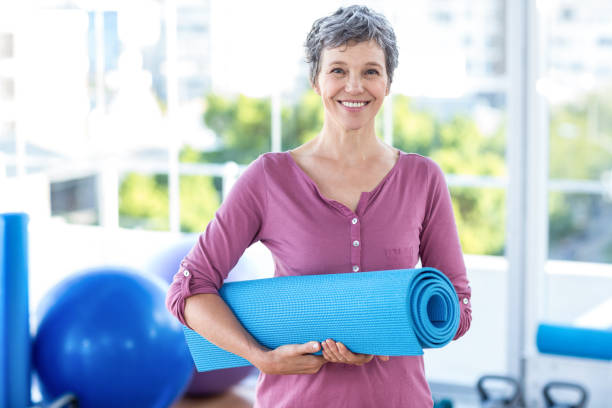 Portrait of mature woman with yoga mat stock photo
