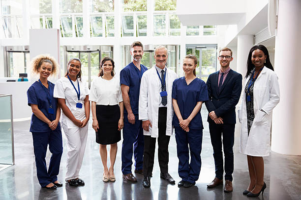 Portrait Of Medical Staff Standing In Lobby Of Hospital - foto stock