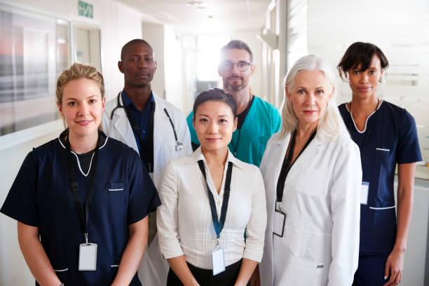 portrait of medical team standing in hospital corridor - anestesista foto e immagini stock