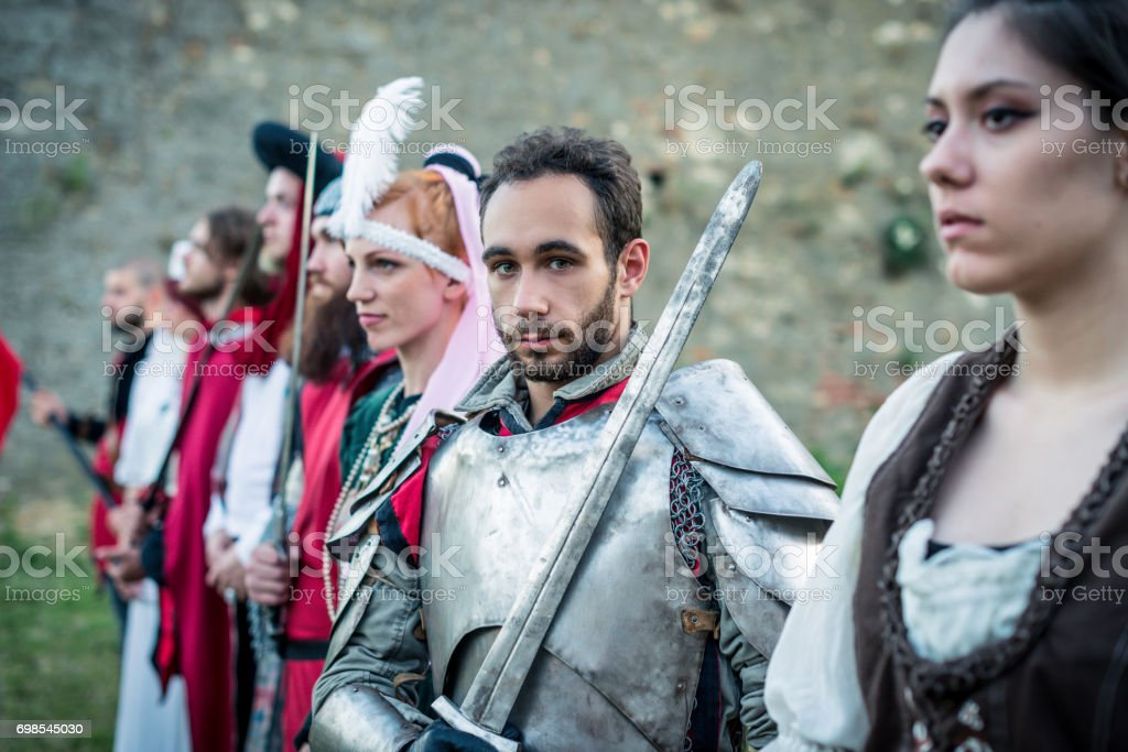 Portrait of medieval knight surrounded by peasants and aristocracy stock photo