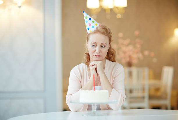 porträt von melancholischen reife frau sitzt alleine am geburtstagstisch mit kuchen, tragen partyhut und suchen traurig - geburtstag vergessen stock-fotos und bilder