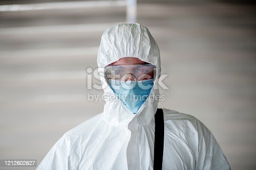 A man is dressed in a chemical protective overalls and a half mask with air filters and safety glasses.