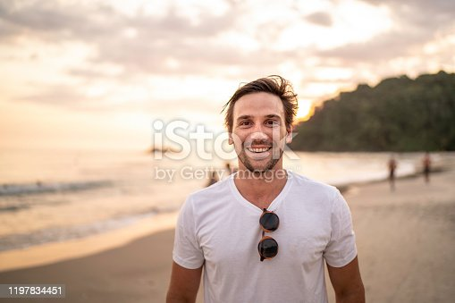 Portrait of men smiling at the beach