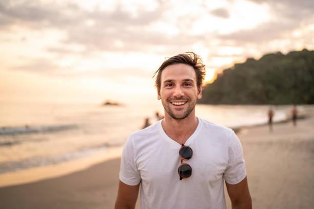 porträt von männern, die am strand lächeln - 30 34 jahre stock-fotos und bilder