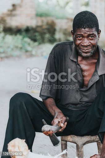 portrait of mid adult african man peeling wood stick for manufacturing tool in village in Malawi
