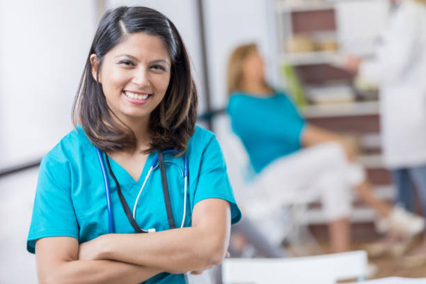 Portrait of mid adult Asian nurse Cheerful mid adult Asian nurse stands confidently in doctor's office or hospital. She has her arms crossed. filipino ethnicity stock pictures, royalty-free photos & images