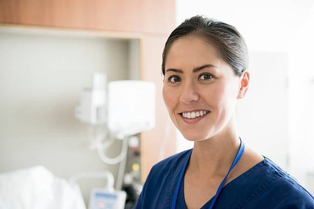 Portrait of mid adult Asian nurse smiling towards camera stock photo