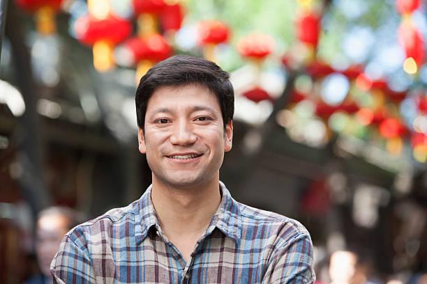 portrait of mid adult man in nanluoguxiang, beijing - mid volwassen mannen stockfoto's en -beelden