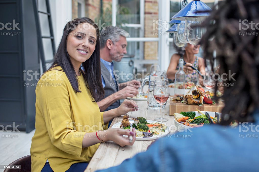 Portrait of mid adult woman having lunch with friends at dining table...