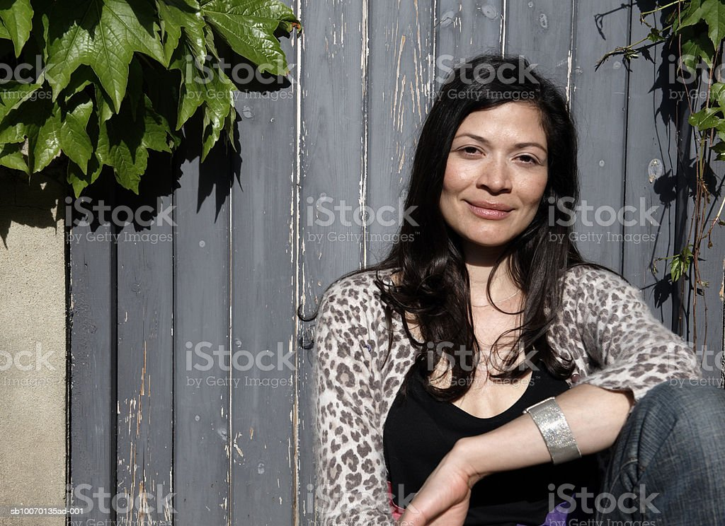 Portrait of mid adult woman leaning against fence royalty-free stock photo