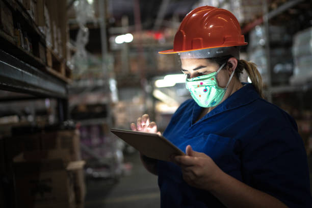 portrait of mid adult woman wearing face mask using digital tablet - working at warehouse / industry - servizi essenziali foto e immagini stock
