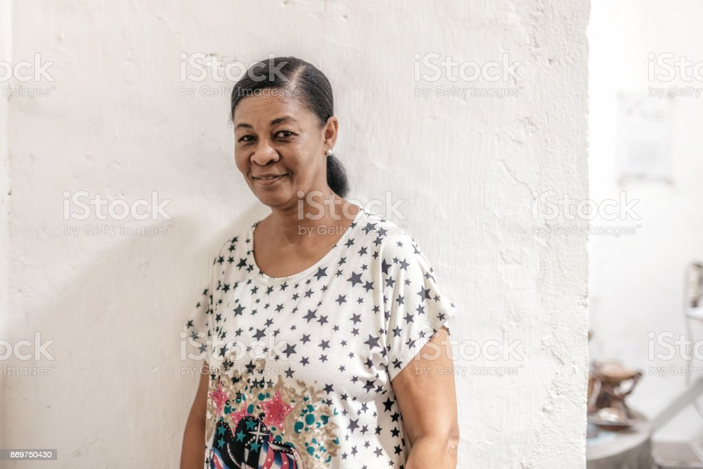 portrait of midaged brazilian woman in front of white wall stock photo