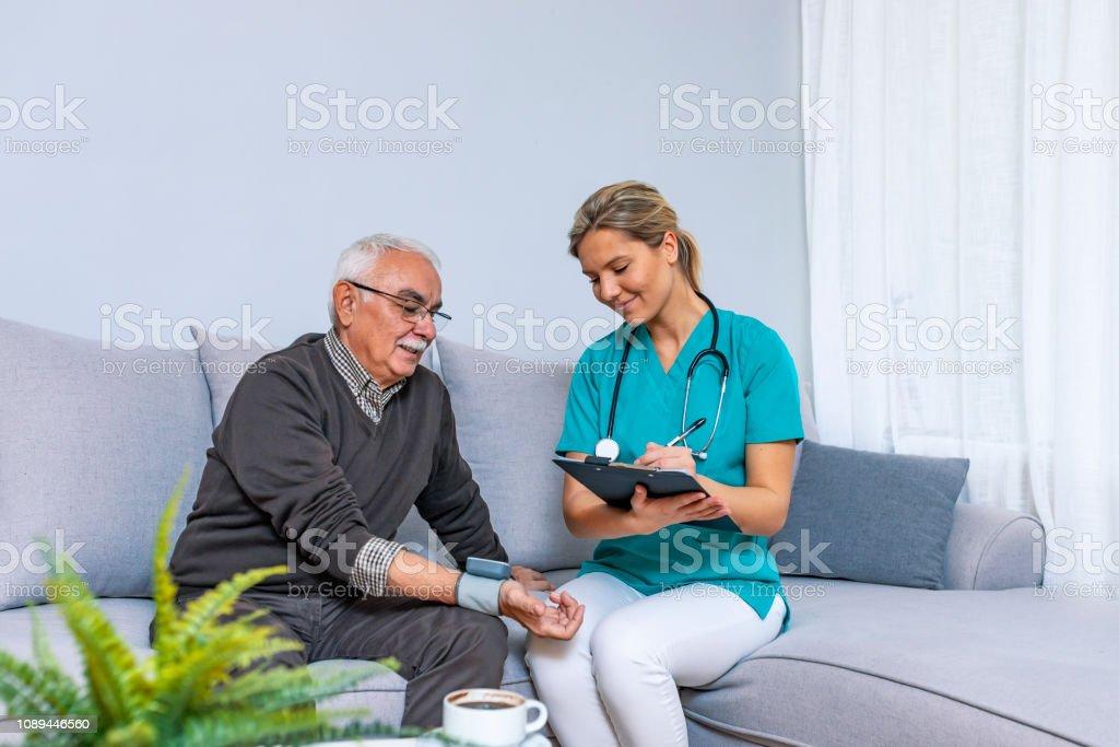 Nurse Visiting Senior man For Check Up. Young nurse measuring blood...