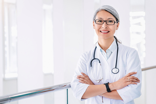 Portrait of middle aged asian female doctor standing in hospital corridor