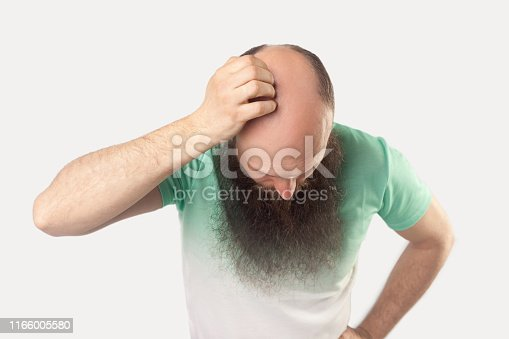 1134770826istockphoto Portrait of middle aged bald man with long beard in light green t-shirt standing and showing his baldness on his head. 1166005580