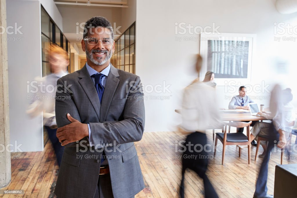 Portrait of middle aged black man in a busy modern workplace stock photo