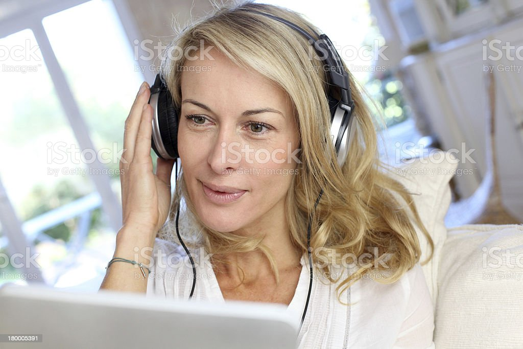 Portrait of middle aged woman relaxing with music stock photo