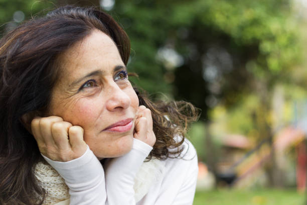 Portrait of middle aged woman with face resting on hands and visionary look stock photo