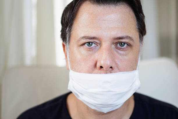 Portrait of middle-aged man wearing his mask incorrectly. stock photo
