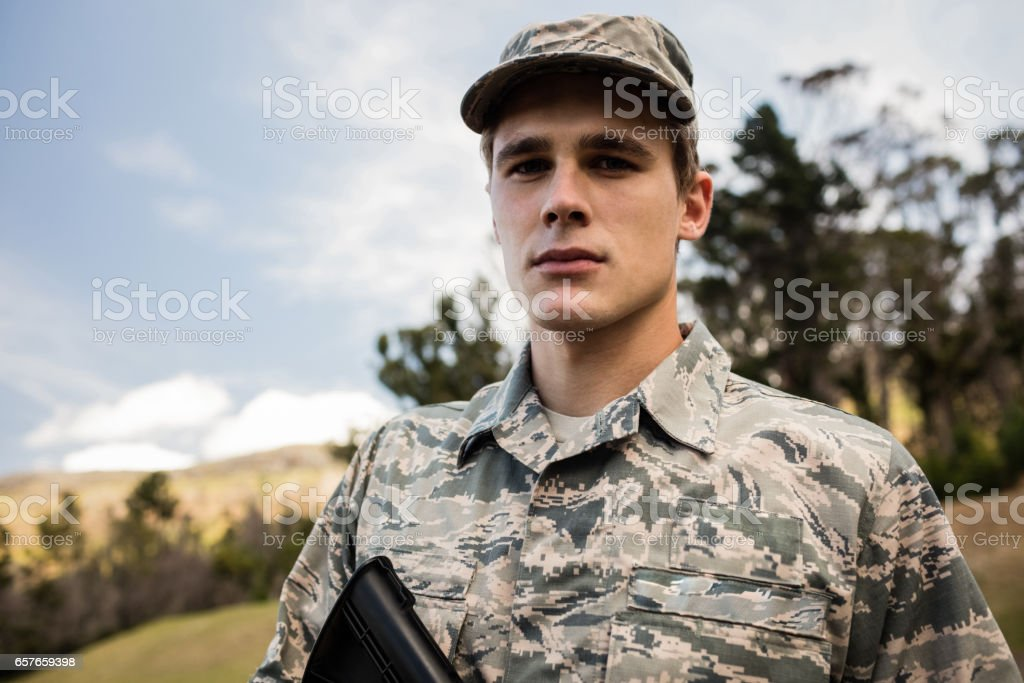 Portrait of military soldier guarding with a rifle stock photo