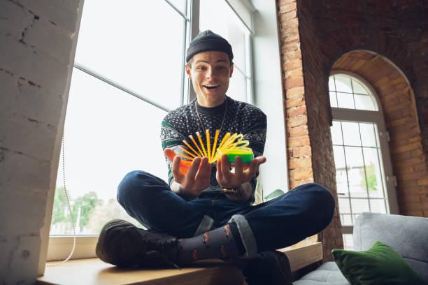 レトロなおもちゃを使ったミレニアル世代の少年の肖像画、過去のものと出会い、楽しんで、虹の春のおもちゃを探索する - gen z ストックフォトと画像