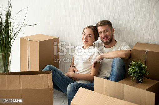 938682826istockphoto Portrait of millennial couple sitting on floor of first home 1044943348