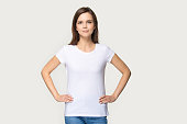 istock Portrait of millennial woman demonstrating white t-shirt for copyspace 1162731082